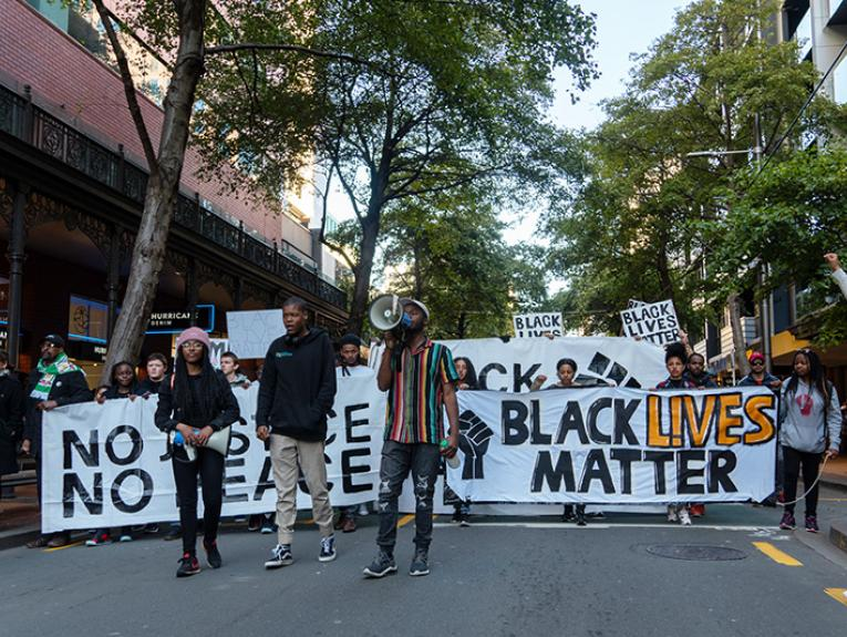 People in front of a Black Lives Matter banner marching in a tree-lined street