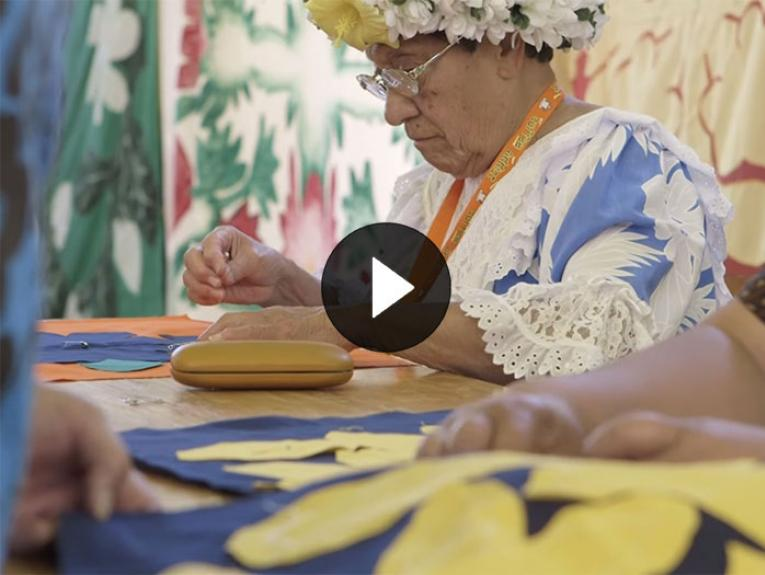 A lady sews a quilted (a Tīvaevae)