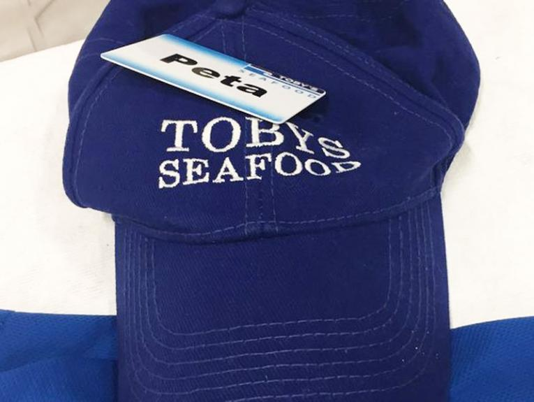 Blue cap with the words 'Toby's Seafood' stitched in white