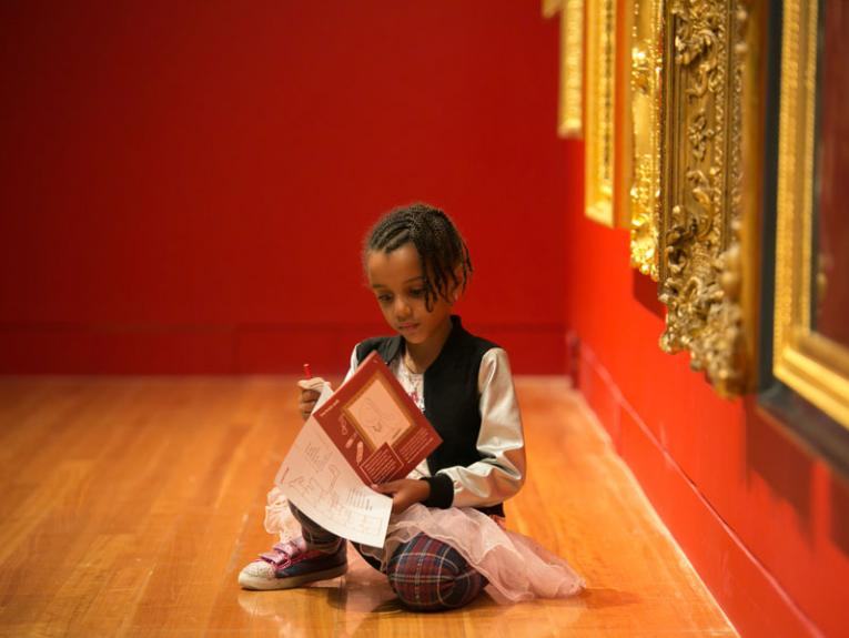 Little girl sits on the floor of an art gallery