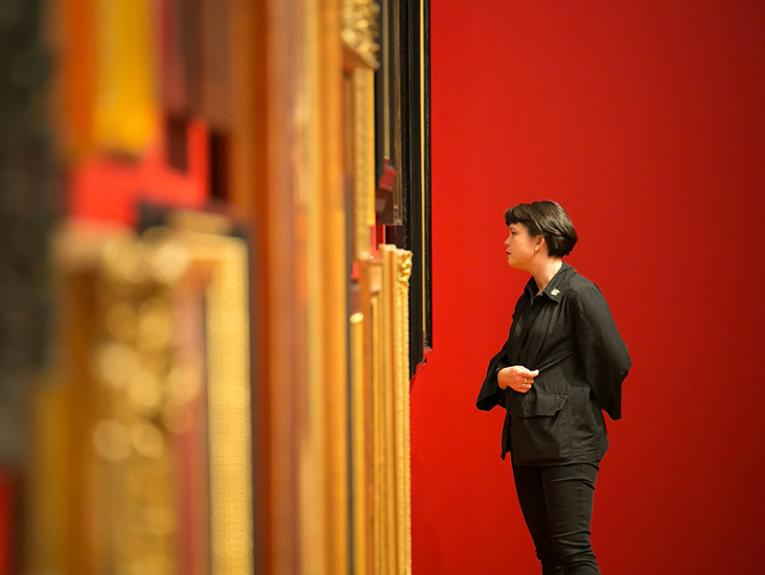 Woman looks at the portrait wall contemplatively