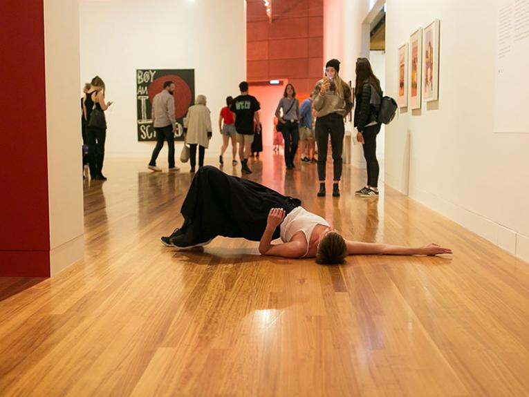 Woman raises her body from the floor in the gallery