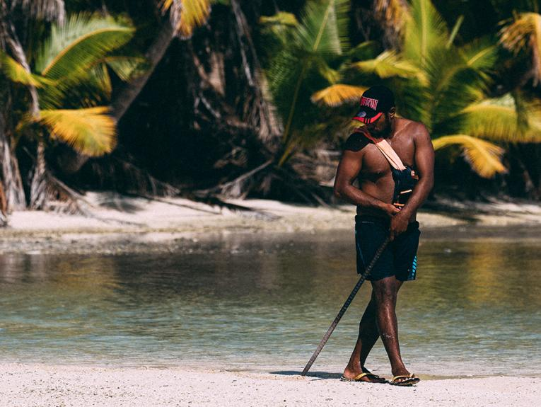 A man wearing shorts and holding a stick is standing on a beach with water and palm trees in the background