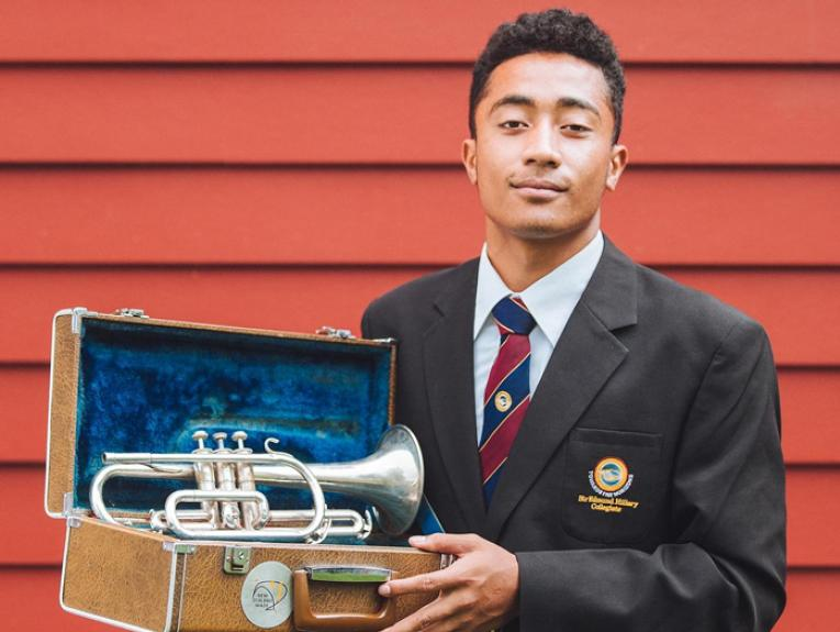 A student stand with a trumpet in a box
