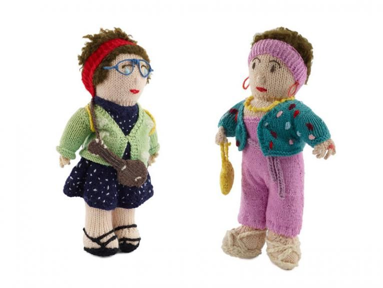 Two knitted dolls. Left: A woman with a red headband, wearing glasses, in a blue dress with white polkadots and a green cardigan. On the right: A woman in pink headband and dungarees with turquoise cardigan and yellow handbag