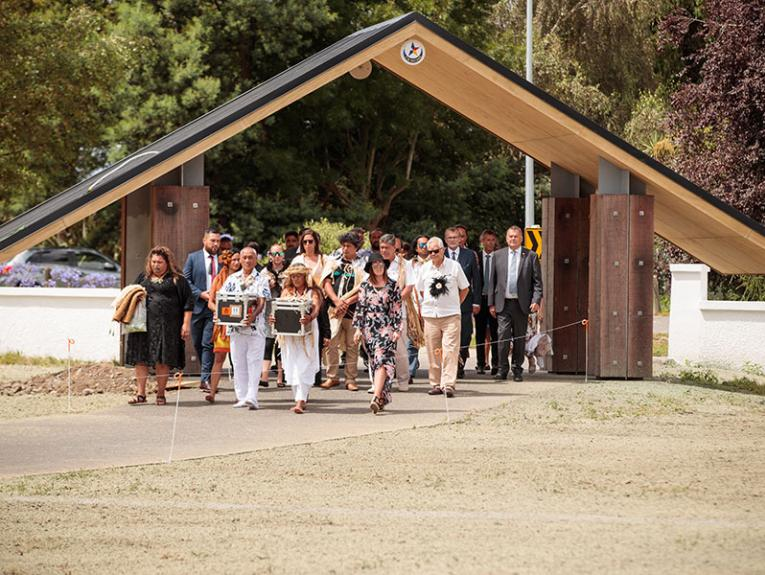 People walk through a gate along a path carrying two boxes of remains