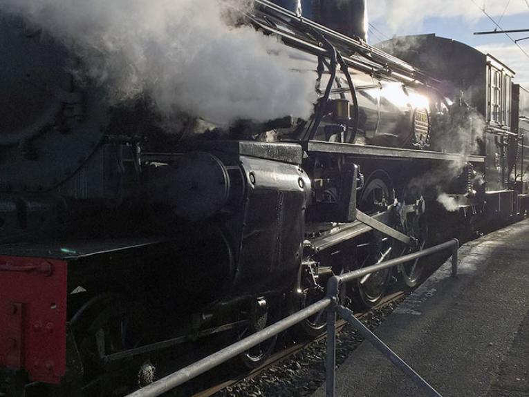 Steam train sits stationary at a station