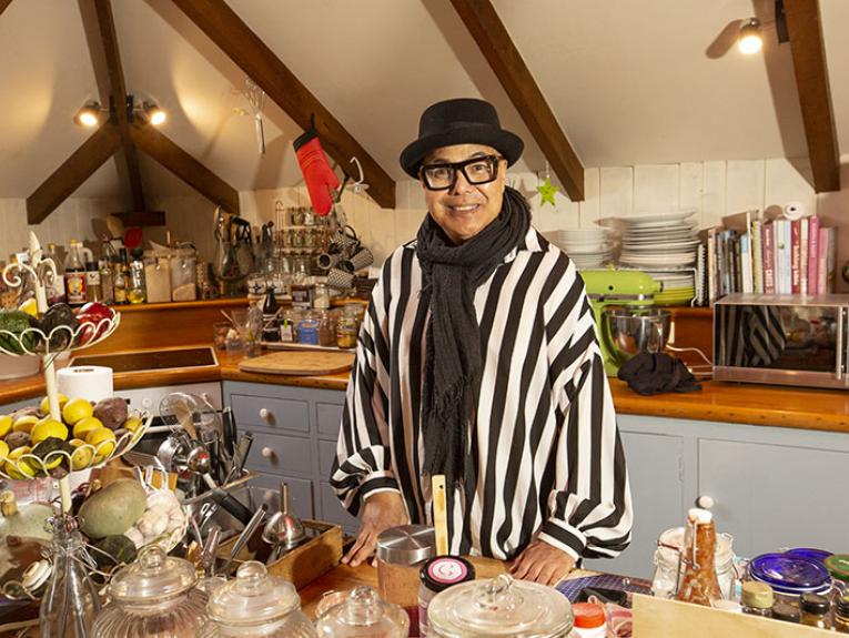 Uncle Pare stands in his kitchen. He wear a black and white striped shirt, black scarf, glasses, and a black brimmed hat. His kitchen is overflowing with a well organised array of bottles, utensils, plates, and jars