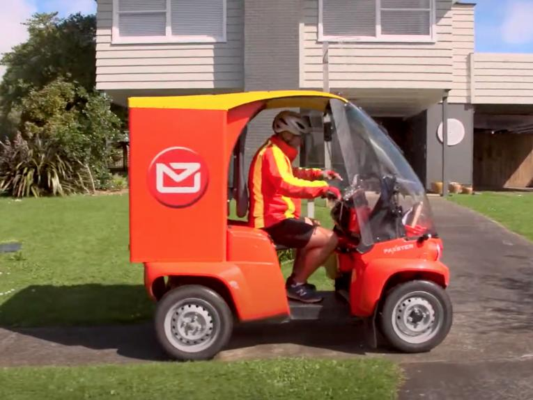 A person driving a red and yellow electric vehicle in front of a house