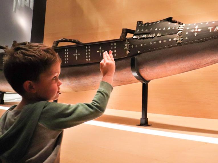 Small child looks at a Pacific vaka