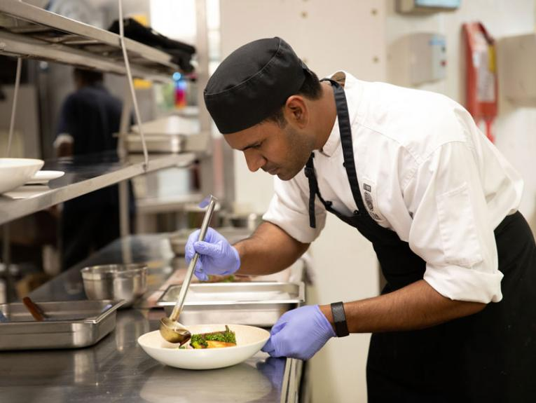 A chef puts the finishing touches to a dish