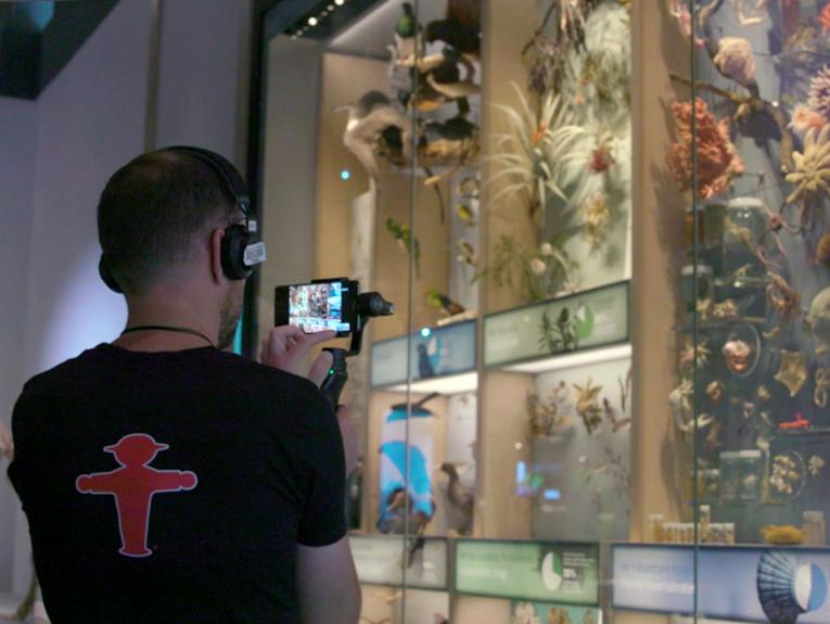 A man holds films a museum display on his phone, he's wearing headphones