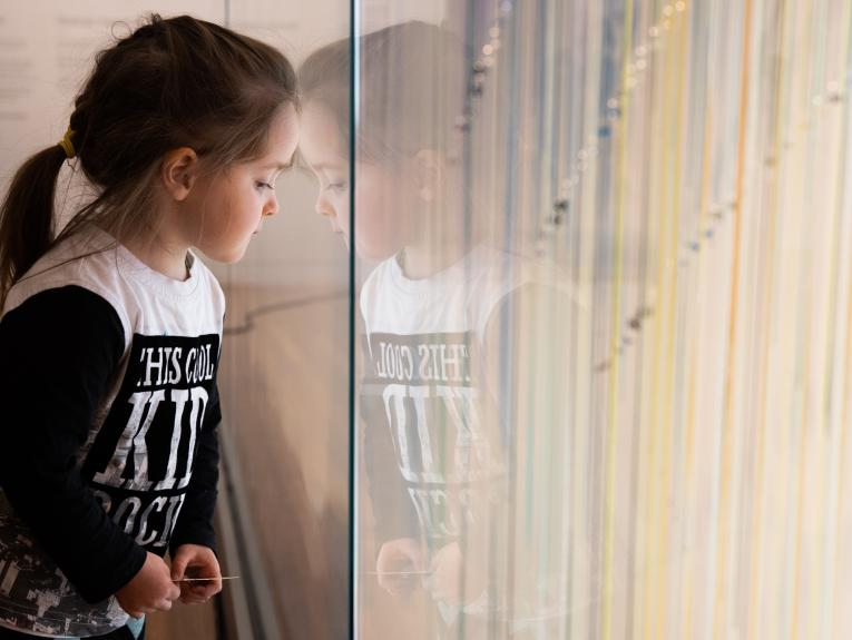Child sitting next to a glass wall looking at coloured ribbons