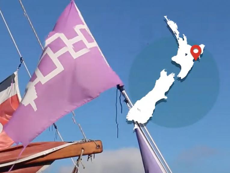 The mast of a boat with sails and map overlaid with a map of New Zealand on the top-right
