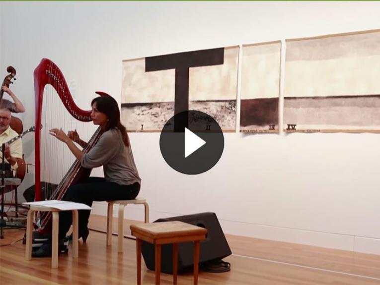 A lady plays the heart in front of Colin McCahon's work