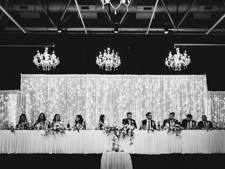 Long table featuring the bridal party is dressed with flowers. Behind them is a white curtains through which you can see fairy lights. Three chandeliers hang from the ceiling