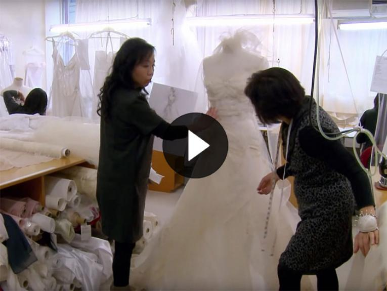 Two ladies work on a wedding dress