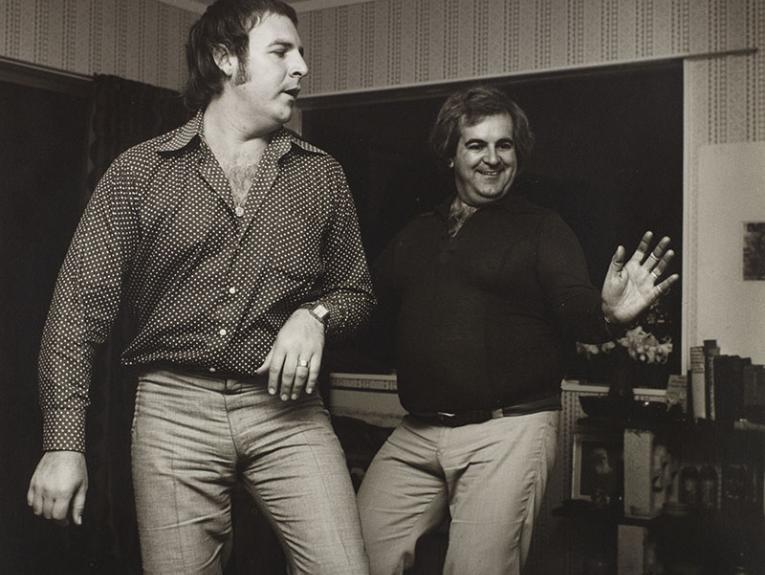 Two men dance in a living room