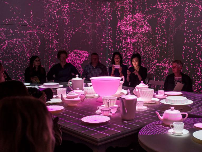 People sat at a table with giant teacups in a pink room