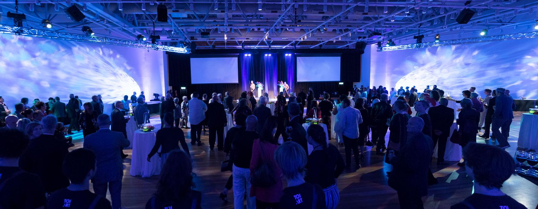 Blue lit function room with lots of people standing