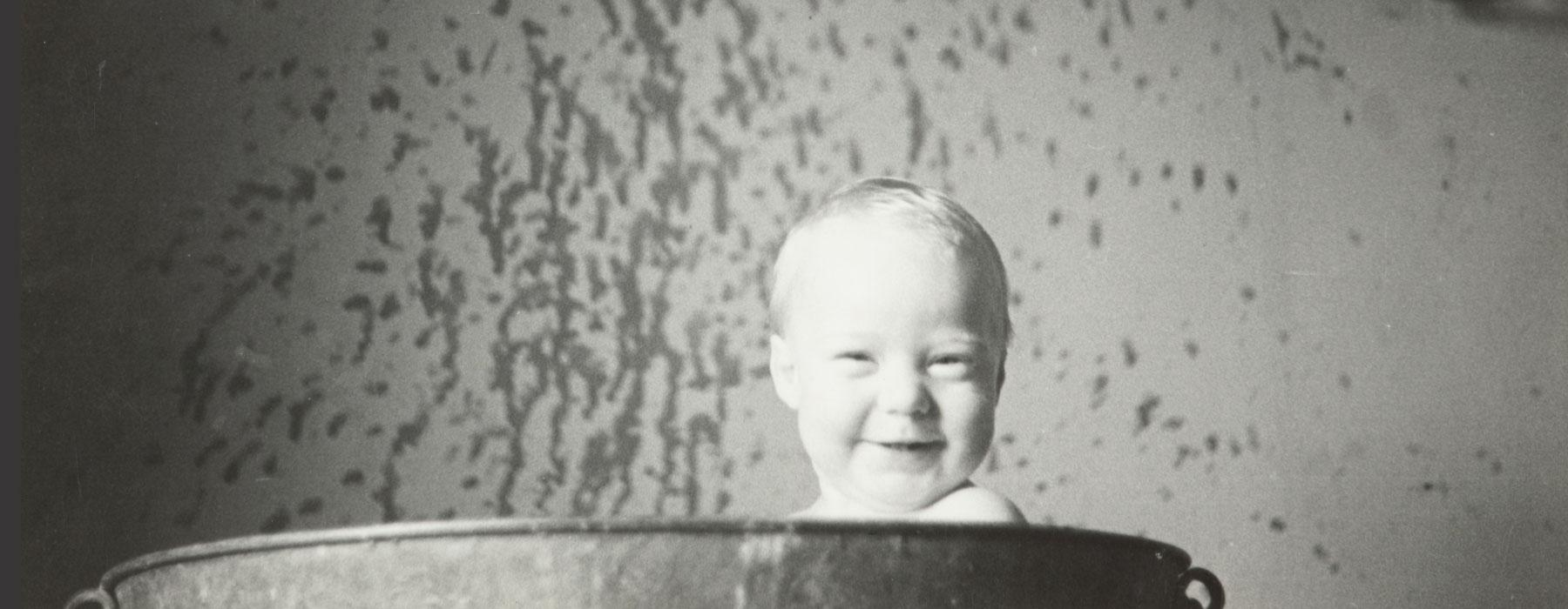 A baby grins, he's poking his head above a bathtub. There's water splashes on the walls.
