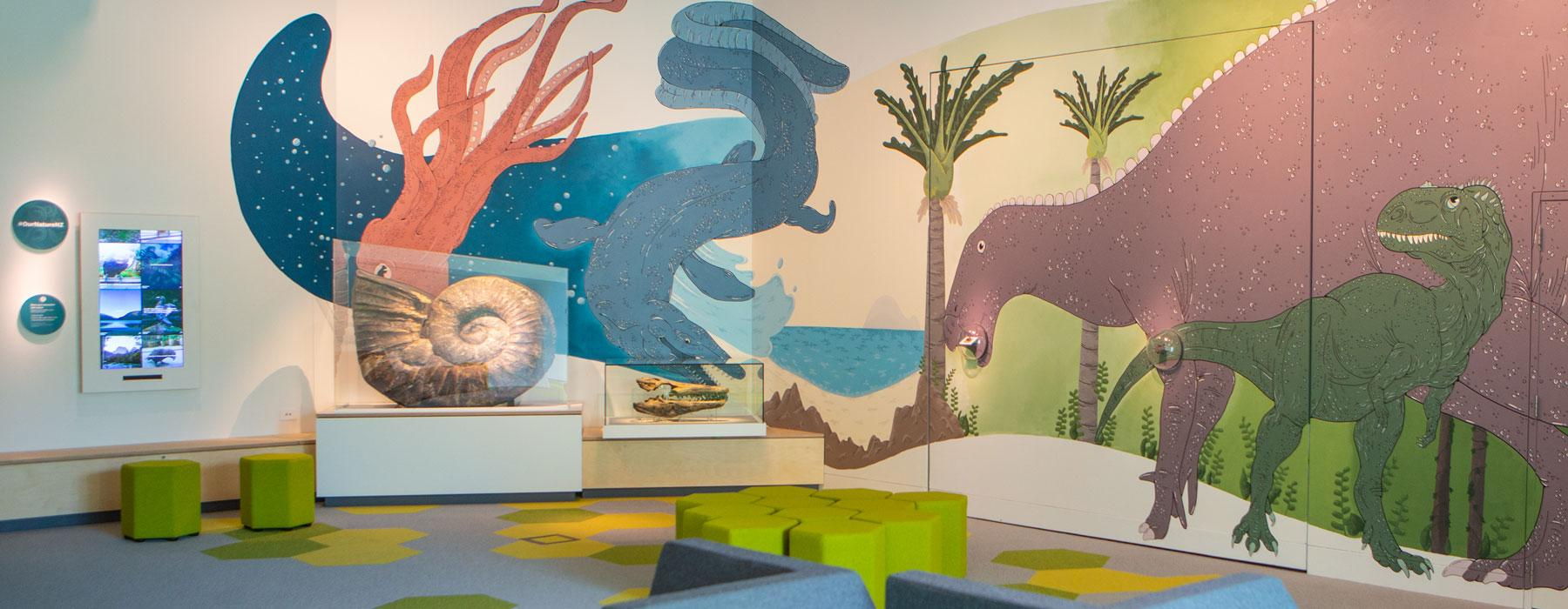 A room with dinosaurs painted on the wall and real fossils displayed