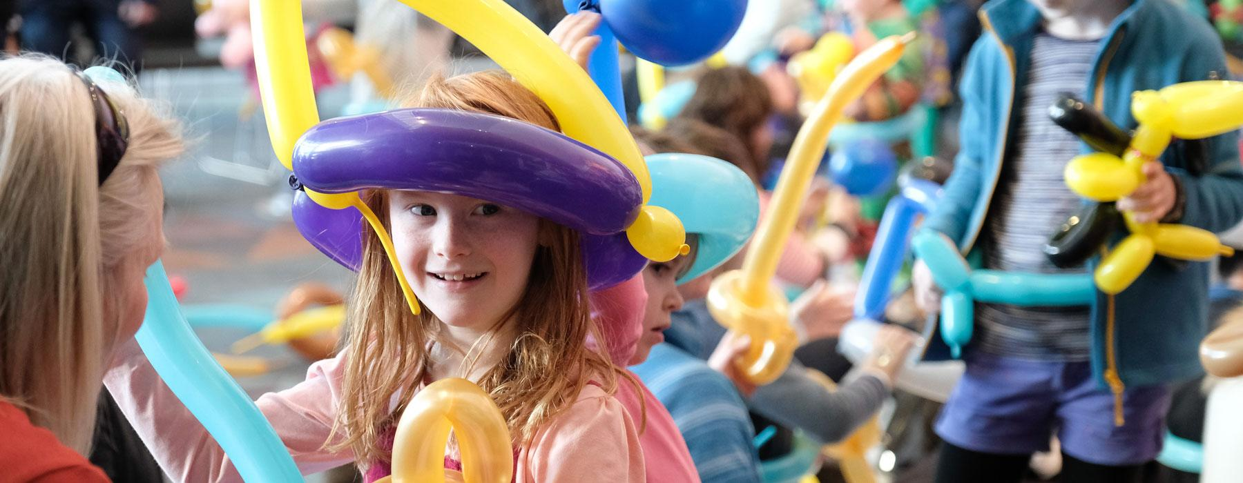 A little girl plays with balloons during a school holiday balloon workshop