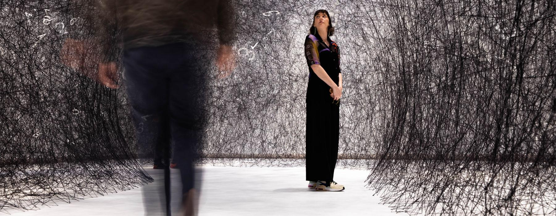 A woman stands amid the artwork, a network of black strands of wool