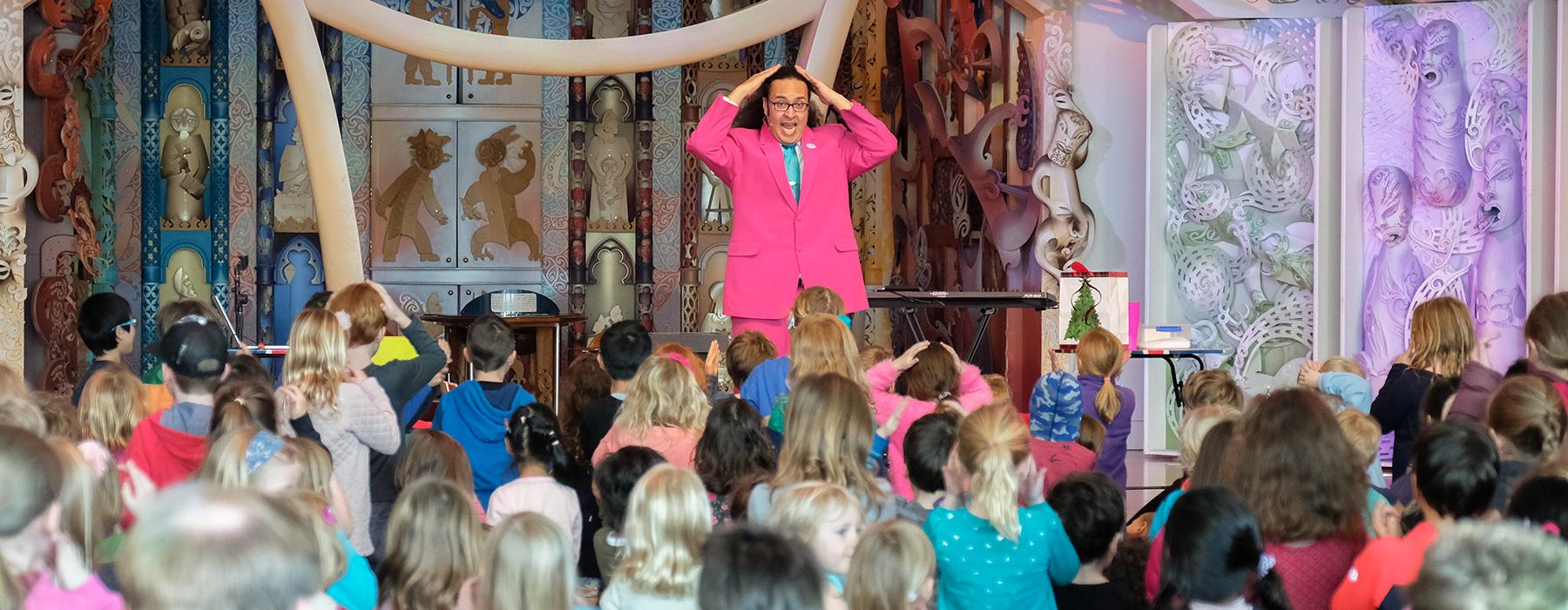 A children's performer surrounded by captivated kids