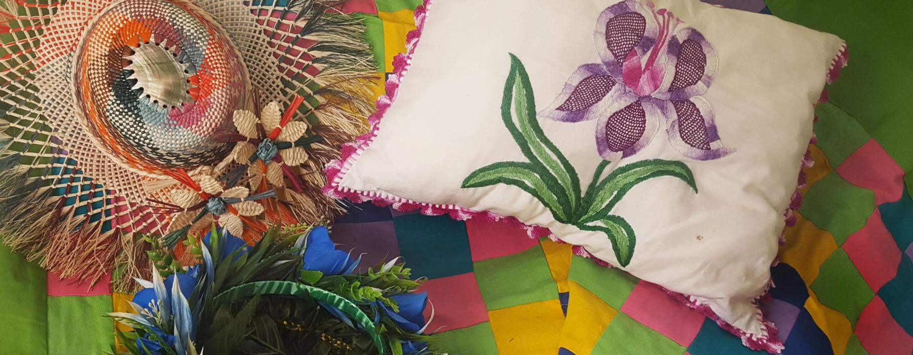 A hat, a cushion and a garland sitting on a colourful quilt for Cook Islands Language Week