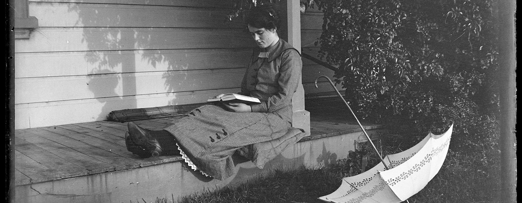 Photo of a woman sitting on her porch reading a book. Beside her an open umbrella sits on the ground.