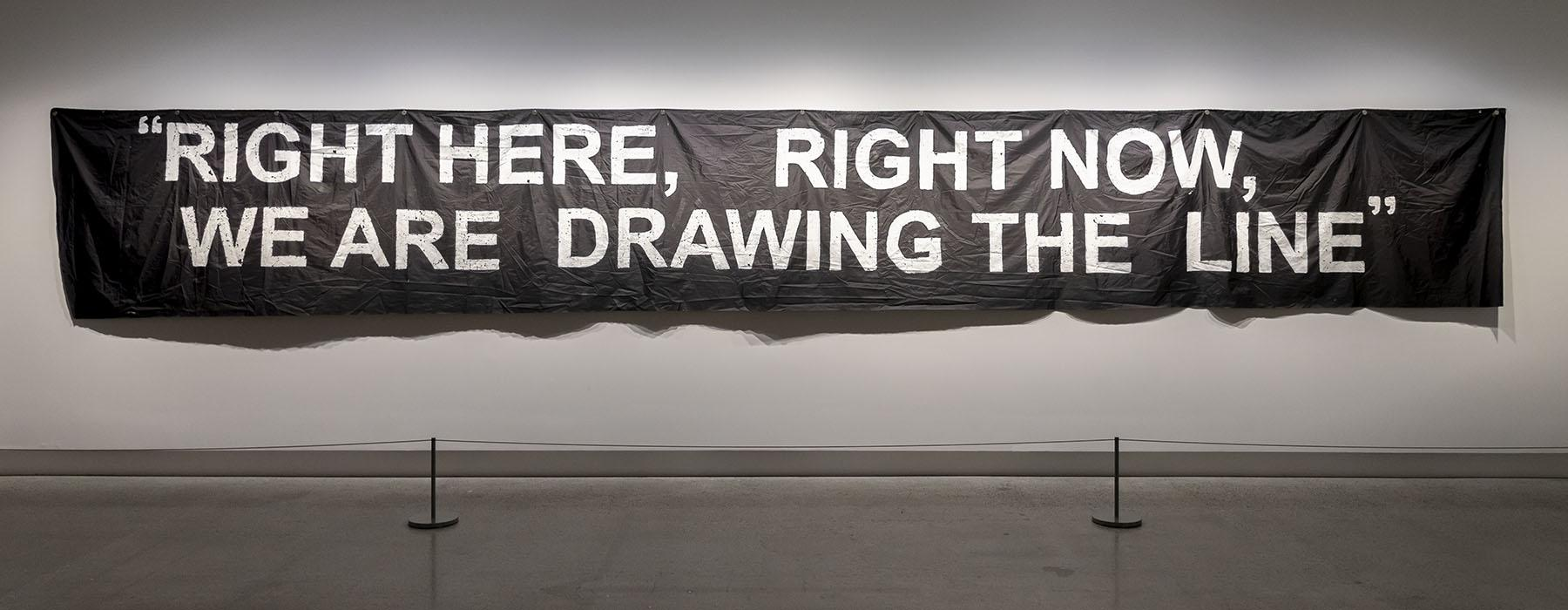 Black banner with the words 'Right here, right now, we are drawing the line' on it, hanging on the gallery wall