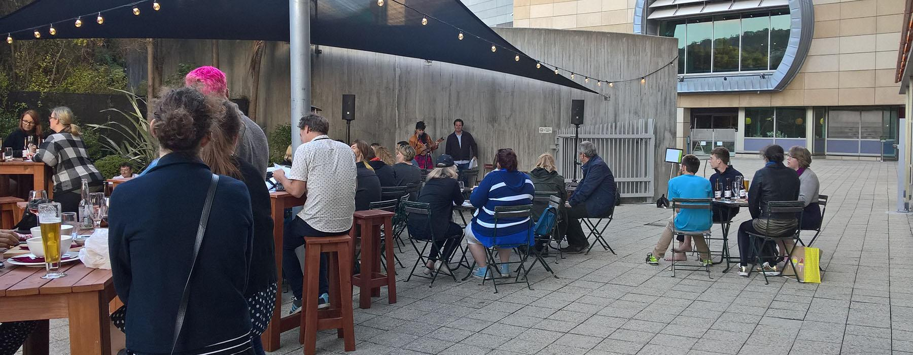 General view of Red Gates bar. People sitting at tables watching two people perform