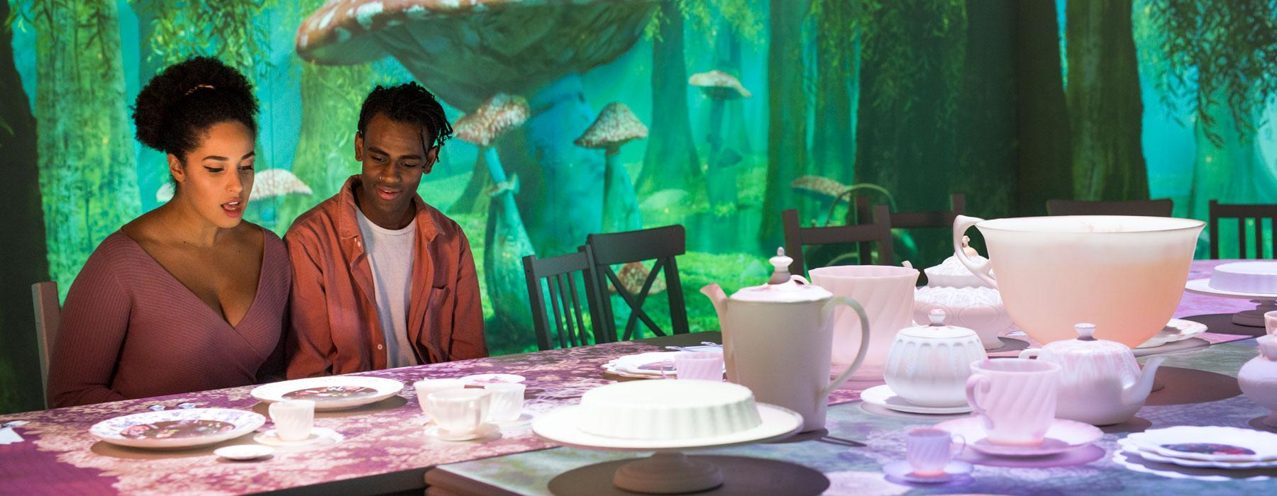 Two people sit at a table with a tea set on it. In the background are projected images of mushrooms and trees
