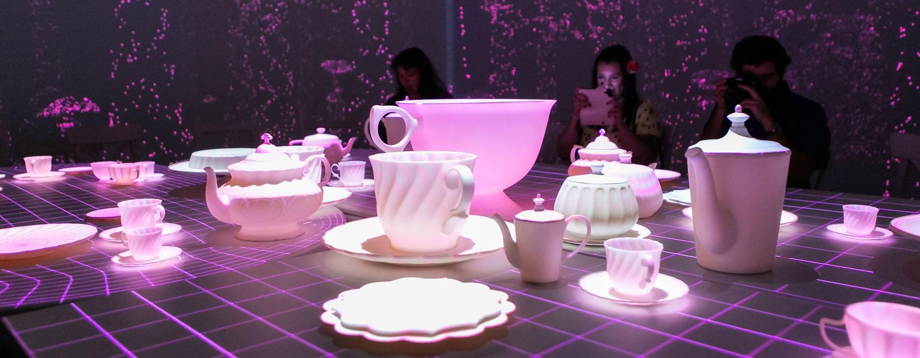 Three people sit at a table with a tea set on it. Digital projections cover the table and the walls.