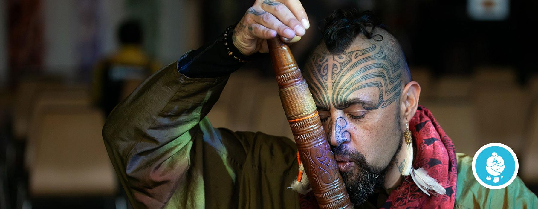 Man plays a Māori musical instrument