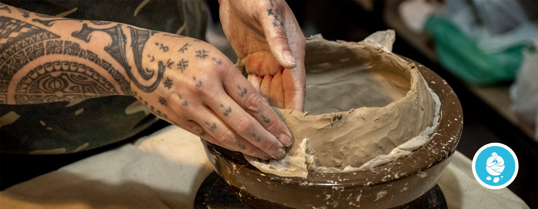 Tattooed hands on a clay pot on a wheel