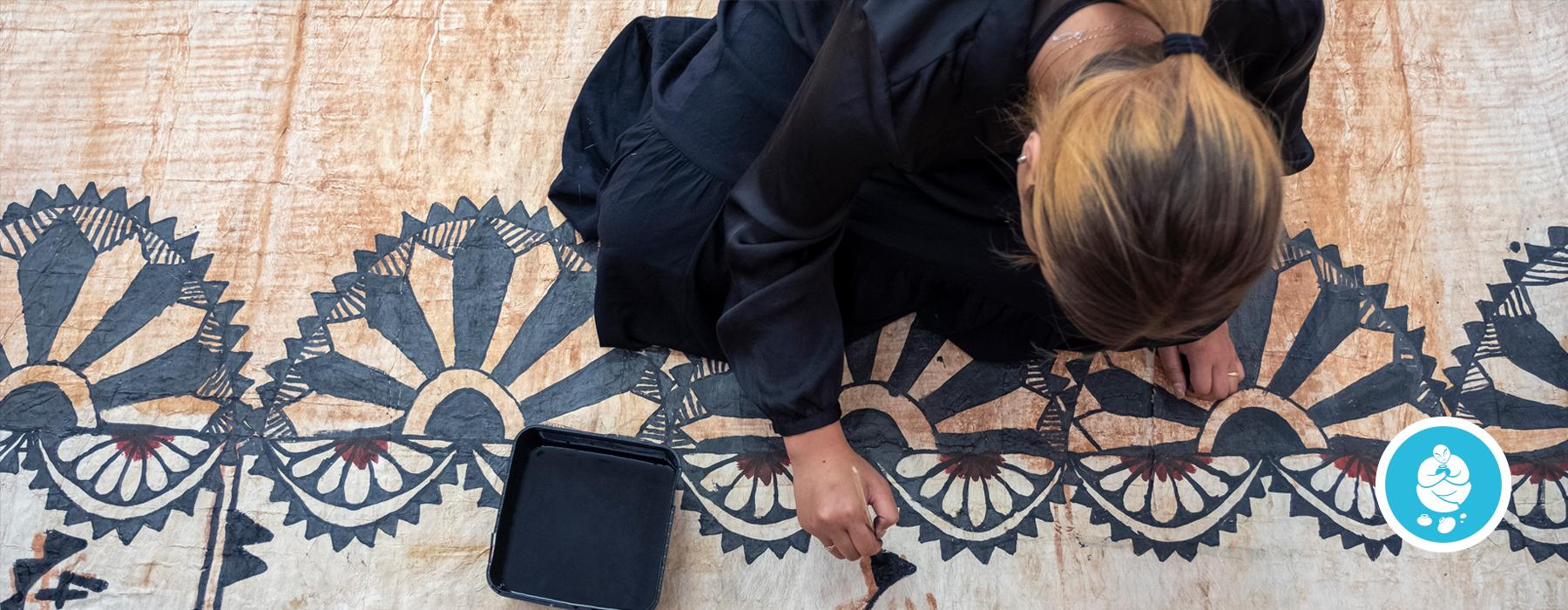A woman crouched on a tapa cloth, painting with black paint