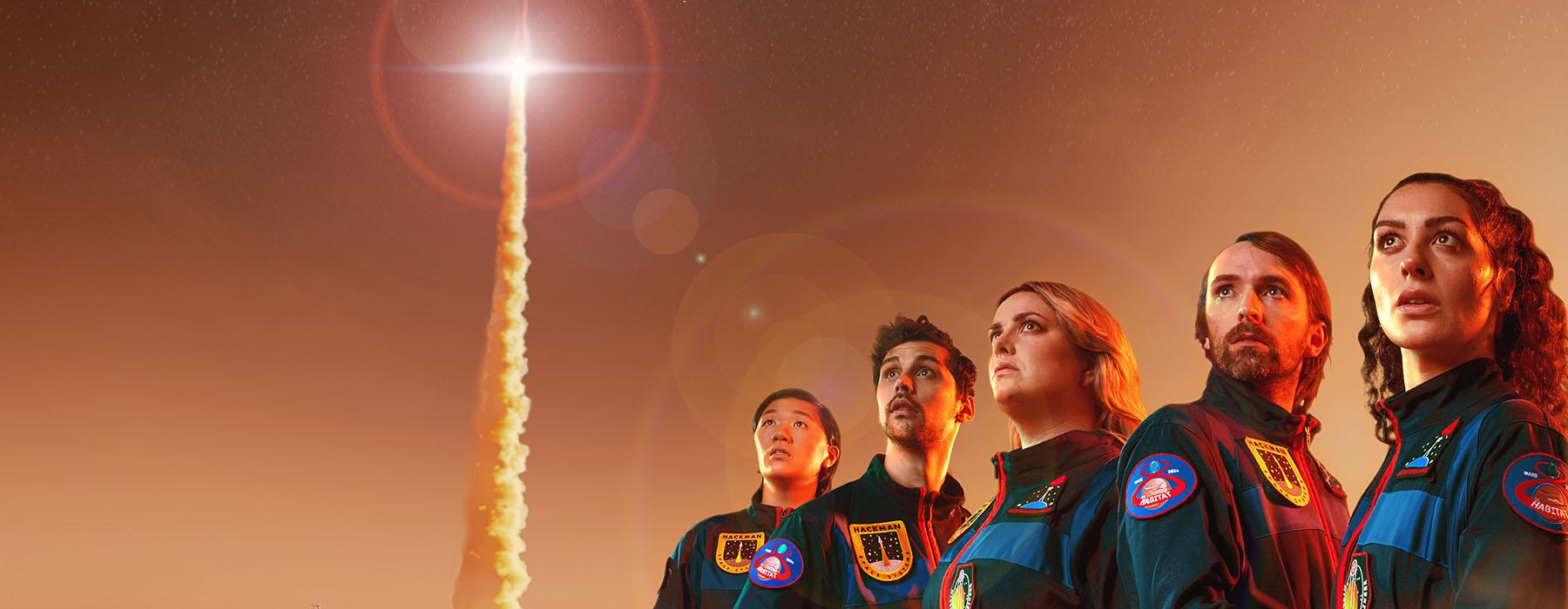 A group of astronauts look to the skies as a rocket takes off. The sky and ground are red, suggesting they are on Mars