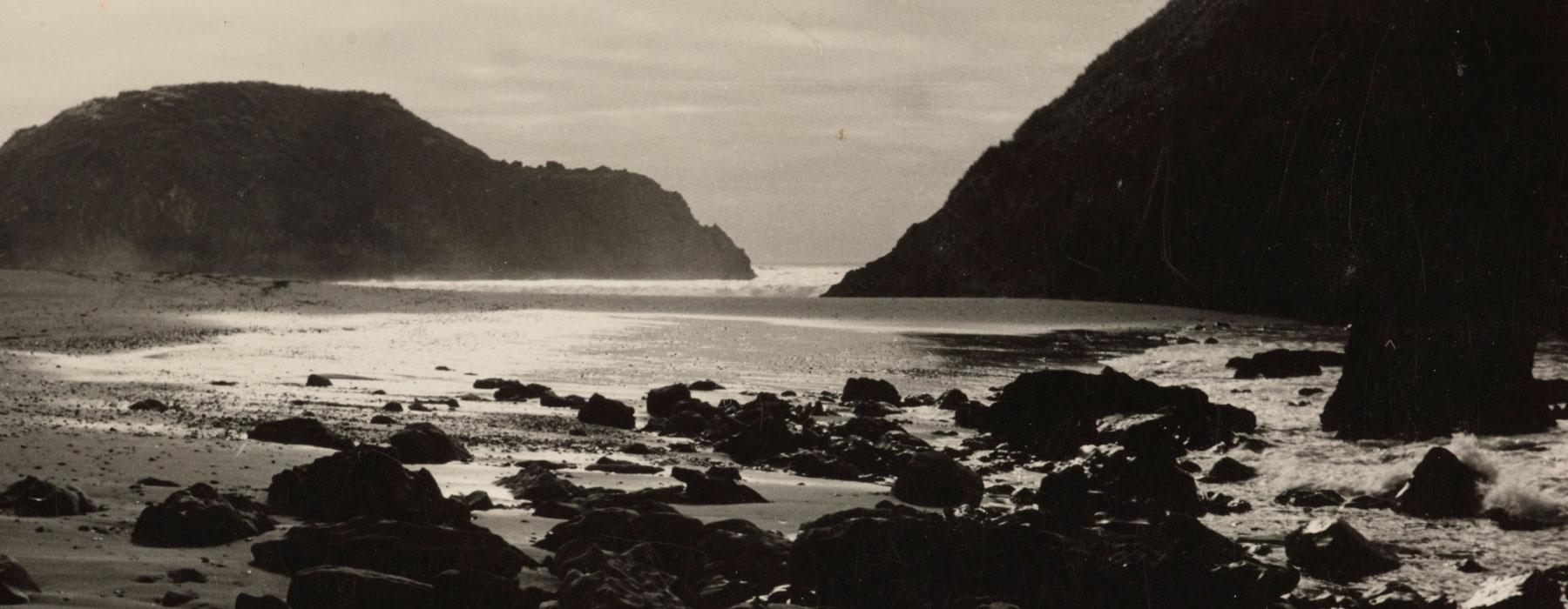 Black and white photograph of a beach and waves