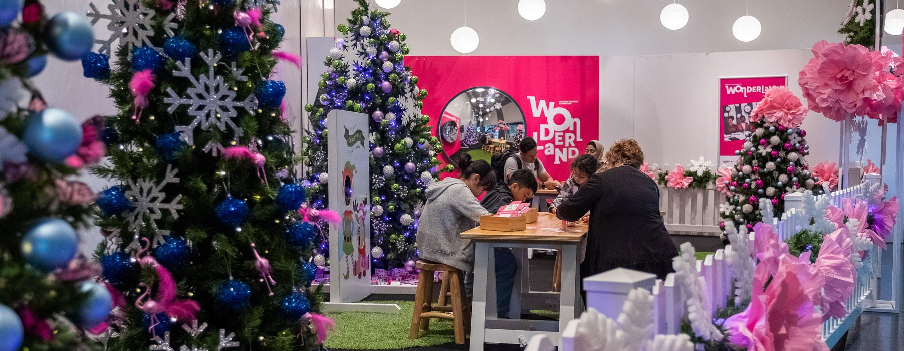 Children and adults doing craft together at a table, lots of Christmas trees surround them