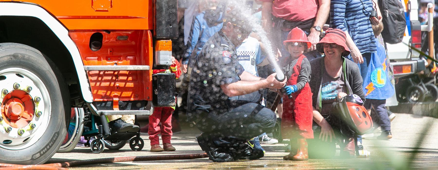 A little boy dressed as a fireman, holds the fire truck hose