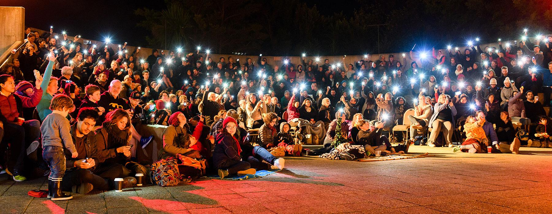 People hold lights above their heads, sat in warm clothes in the dark