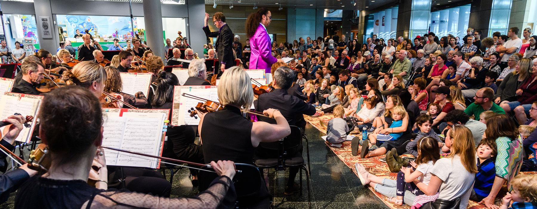 An orchestra performs to an audience