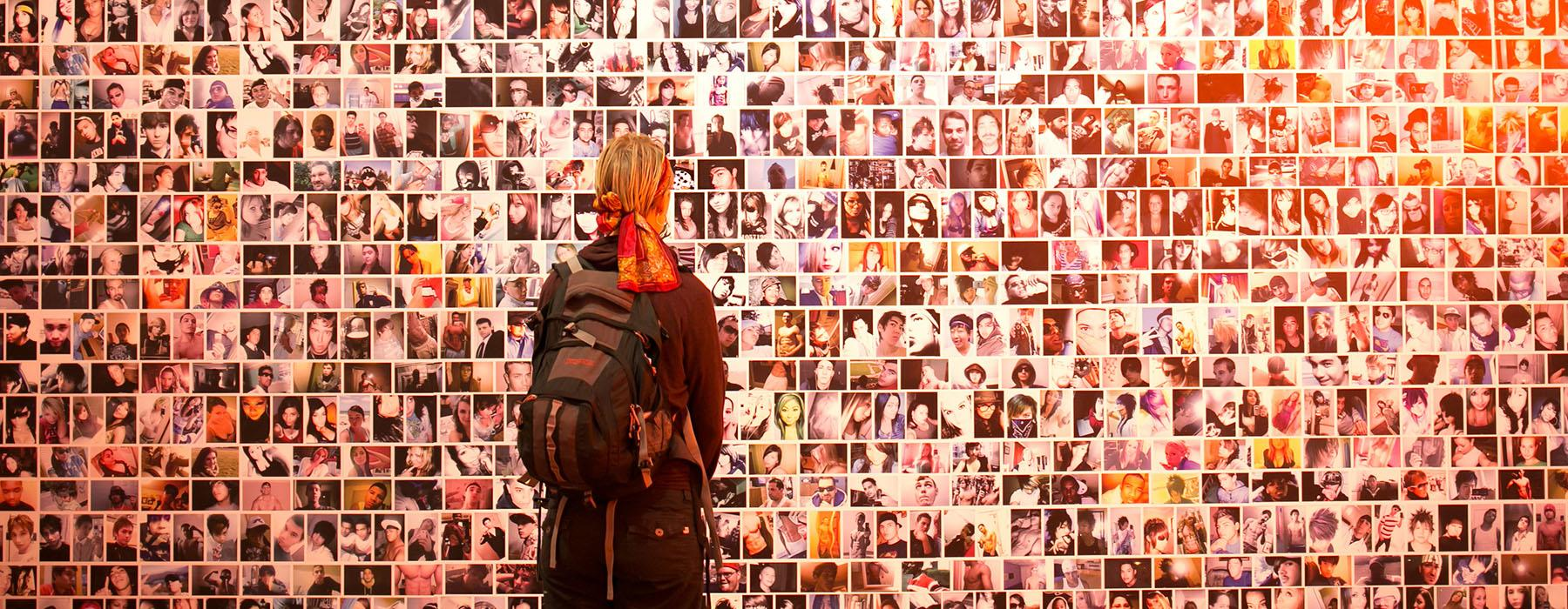 A woman stands in front of a wall of selfie photos