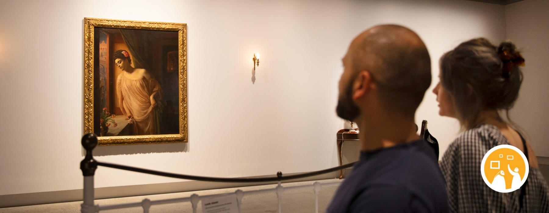two people looking at a gilt-framed painting on a wall