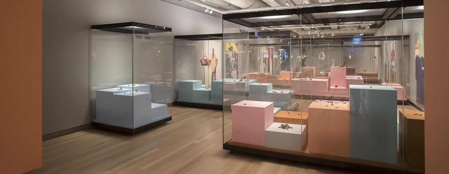 View of Lisa Walker's exhibition including multiple cabinets filled with colourful plinths and jewellery on them
