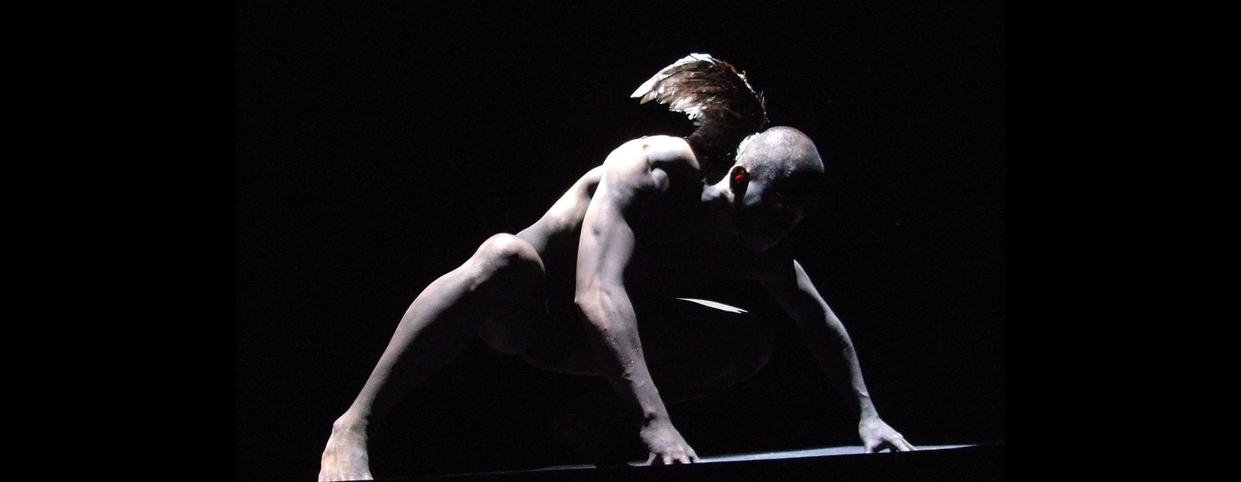 A man down on all fours with small wings stands on stage, the lighting is dark and lit from behind and obscures his face