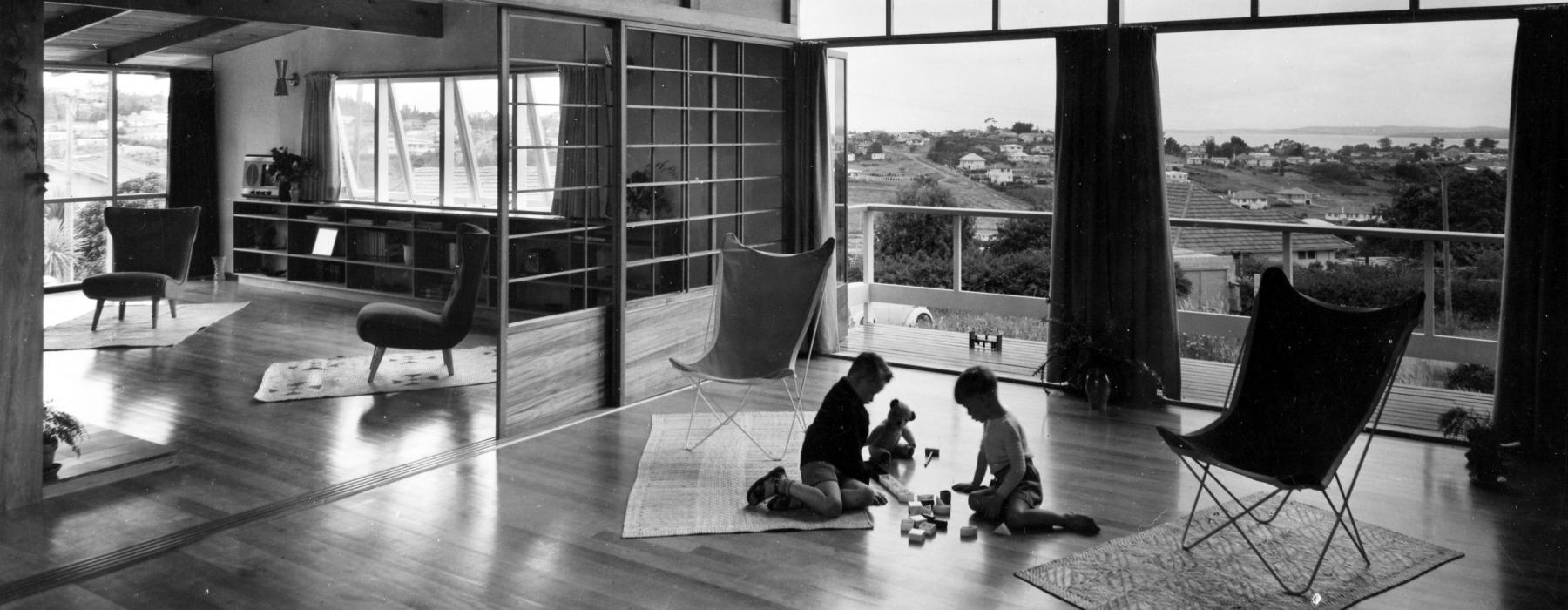 Black and white photo of two children playing on the floor of a large room with a view of other houses and the harbour