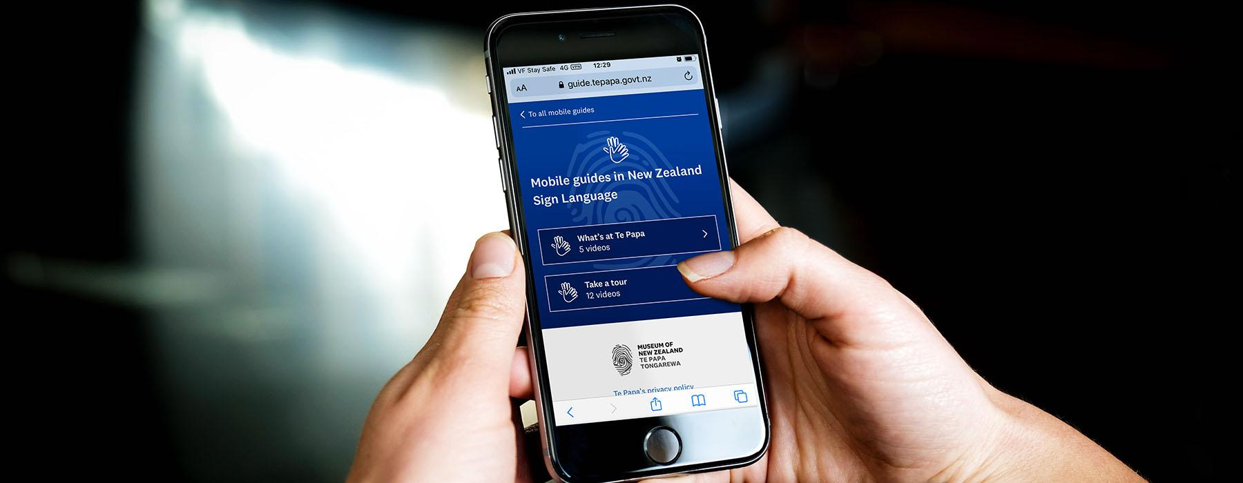 Closeup of hands holding a mobile phone which is displaying the NZSL mobile guide